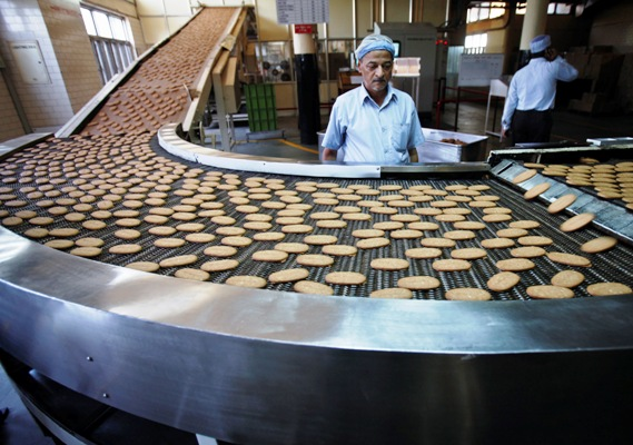 A worker stands next to a production line at the Britannia biscuit factory in New Delhi.