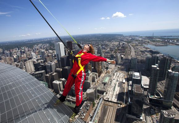 A reporter leans over the edge of the catwalk during the media preview for the EdgeWalk on the CN Tower in Toronto.