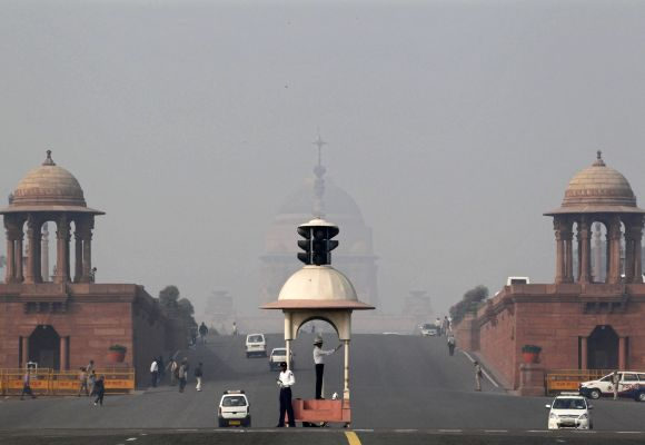 A traffic police officer directs traffic in front of India's presidential palace Rashtrapati Bhavan amid dense smog in New Delhi.