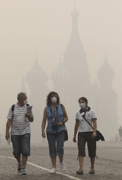 Tourists, wearing masks to protect themselves from heavy smog, walk along Red Square in central Moscow.