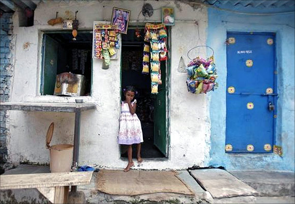 A girl stands at the door of a grocery shop at a slum in New Delhi.