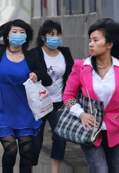 Women wearing face masks run to cross a street on a heavy haze day during winter in Beijing.