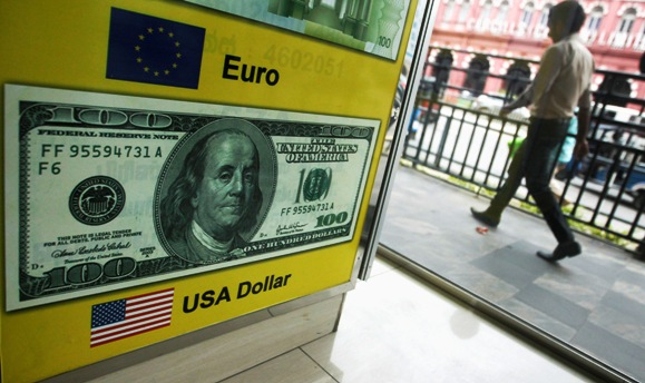 A man walks past a board advertising US dollars at a money exchange shop in Colombo.