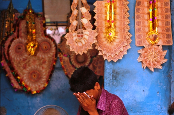 A vendor wipes his face at a shop selling garlands made of Indian currency notes in the old quarters of Delhi.