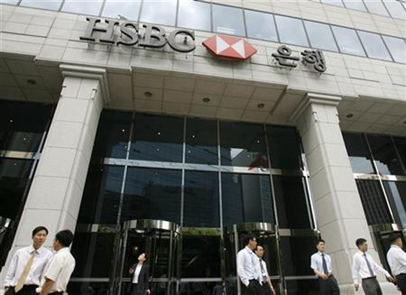 People walk past a branch office of HSBC in Seoul.