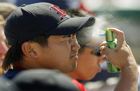 Red Sox pitcher Daisuke Matsuzaka sprays sunscreen on his face during a spring training game against the Dodgers in Vero Beach, Fla.