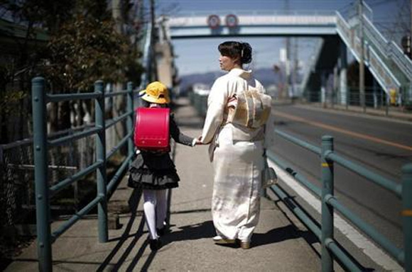 A girl walks with her mother after her first day of school at the Shimizu elementary school in Fukushima, northern Japan.