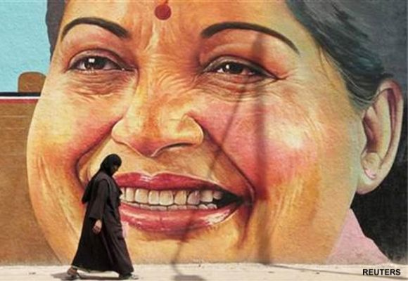 A woman walks past a portrait of J. Jayalalithaa, Chief Minister of the southern Indian state of Tamil Nadu.