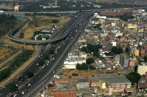 A picture taken from the window of passenger airplane shows traffic on a road in New Delhi.