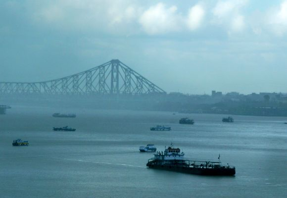 A passenger boat moves along the Hooghly river after passing under the Howrah bridge during a monsoon shower in the eastern Indian city of Kolkata.