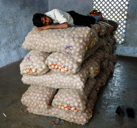 A trader sleeps on sacks of onions at a wholesale market in Ahmedabad.