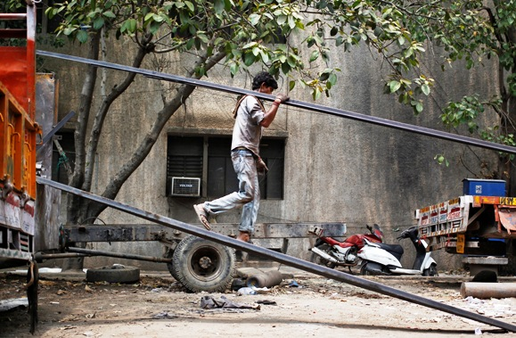 A labourer unloads an iron rod from a truck.