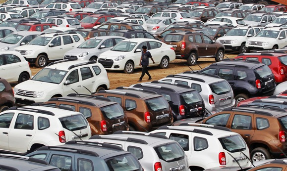 A worker walks past parked Renault cars at its stockyard on the outskirts of Ahmedabad.