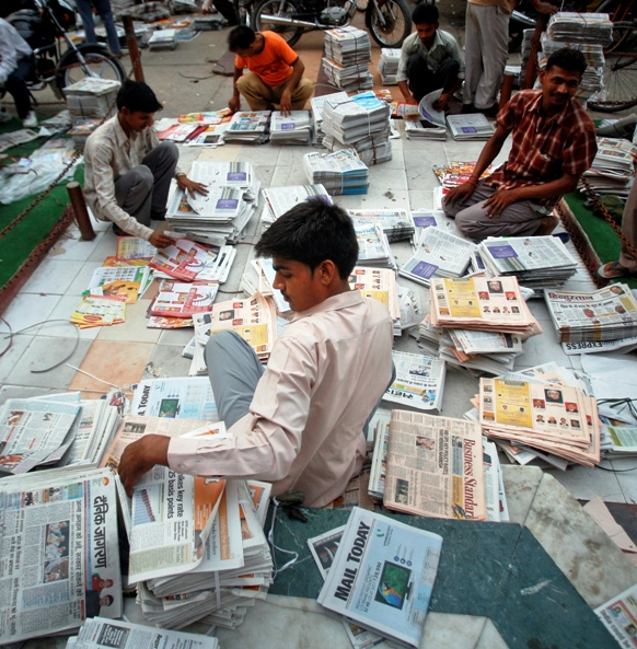Distributors sort through newspapers before selling them during early hours in Noida.