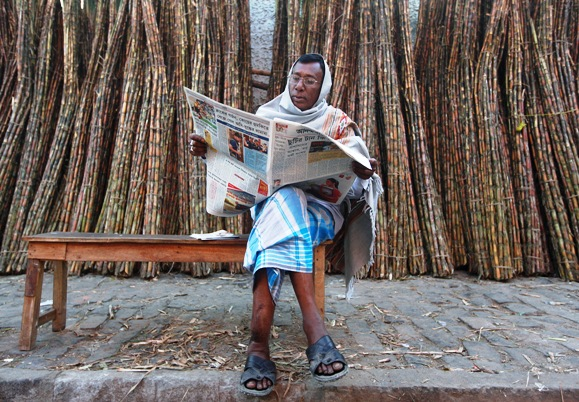 A trader reads a newspaper at a sugarcane wholesale market in Kolkata.
