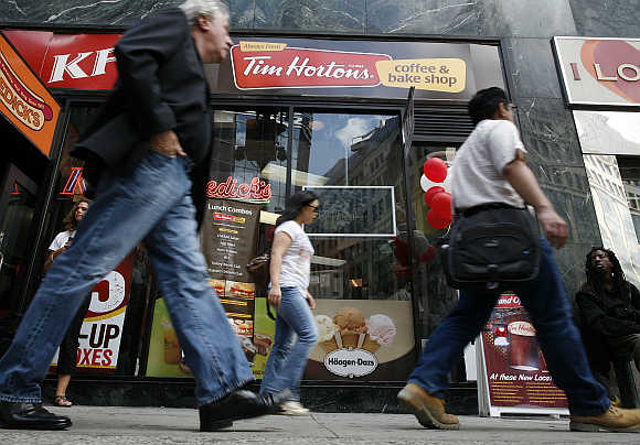 Pedestrians walk past Tim Hortons coffee and bake shop in Midtown Manhattan section of New York.