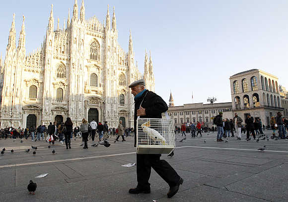 A man carries a cage with a parrot inside it in Duomo Square in downtown Milan.