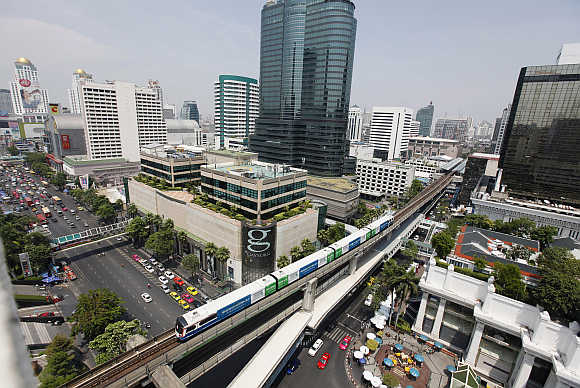 A skytrain passes over vehicles in Bangkok.