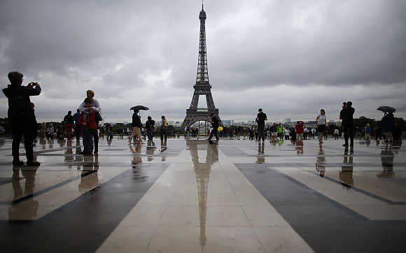 Tourists stroll on the Trocadero square, in front of the Eiffel Tower, during a rainy summer day in Paris.