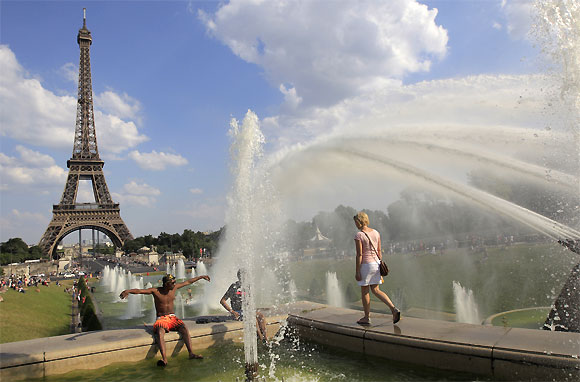 People cool off in a fountain at the Trocadero Square in front of the Eiffel Tower on a warm summer afternoon in Paris.