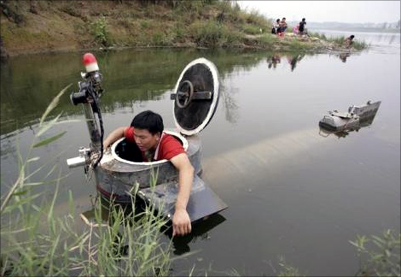Tao Xiangli gets out of his homemade submarine after operating it in a lake on the outskirts of Beijing.