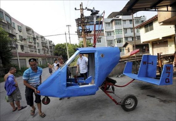 Wen Jiaquan (2nd L), 54-year-old motorcycle mechanic, moves his self-made helicopter in Qingping township of Chongqing municipality.