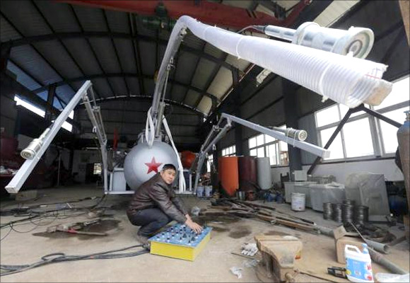 Zhang Wuyi looks up as he squats under a suction pipe of his new submarine that captures sea cucumbers at his workshop in Wuhan, Hubei province.