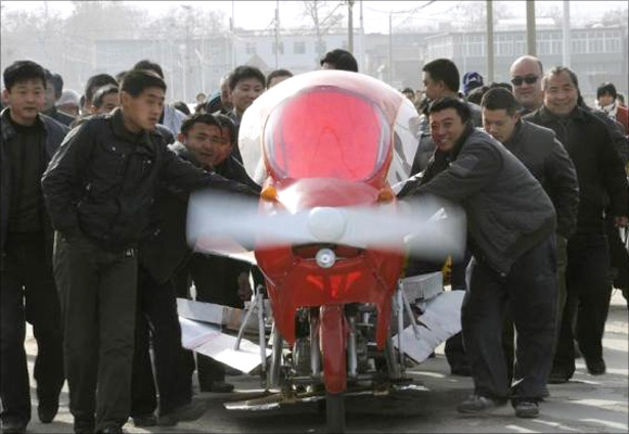 Villagers help to push Zhang Xuelin's self-made aircraft before its test flight in Jinan, Shandong province.