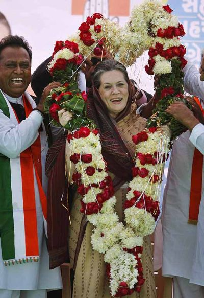Local leaders of the congress place a garland around their party chief Sonia Gandhi.