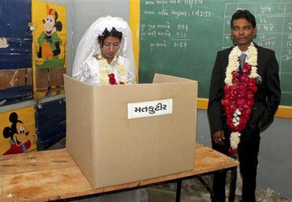 Christina Christian (L), a newly married bride, casts her ballot as her husband Kinjan Tailor stands inside a polling booth.