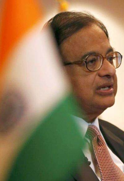 India's Finance Minister Palaniappan Chidambaram speaks behind the Indian national flag.