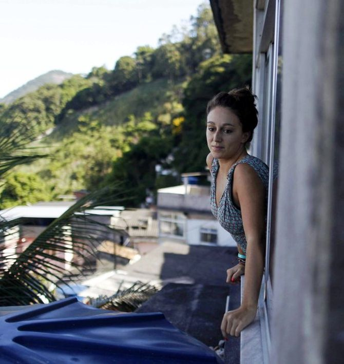 French student Melodie Valerio looks out the window of her rented room in the Pereira da Silva slum in Rio de Janeiro.