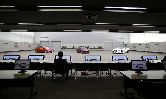 Toyota's Managing Officer Tokuo Fukuichi looks at Auris, left, a clay model of concept vehicle NS4, centre, and luxury brand Lexus, left, inside a decision room at the company's design centre building in Toyota, central Japan.