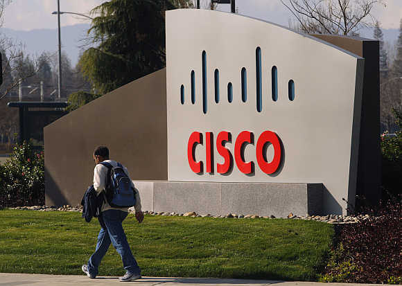 A pedestrian walks past the Cisco logo at the technology company's campus in San Jose, California.