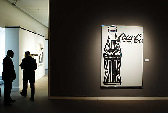 Security guards stand near 'Coca-Cola [4] Large Coca-Cola' by Andy Warhol during a preview of Sotheby's Impressionist & Modern Art auction in New York.