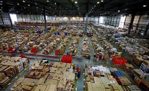 Workers sort through packages at the Amazon warehouse in Milton Keynes in England.