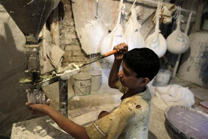 Ten-year old Murtaza works inside a lime paste factory in a slum area in Mumbai.
