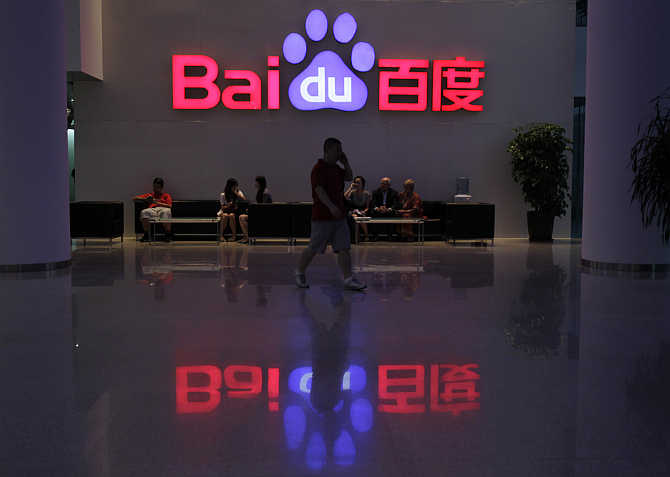 A employee uses his mobile phone as he walks past the company logo of Baidu at its headquarters in Beijing.