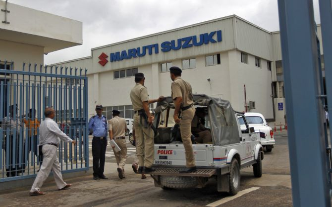 A vehicle carrying Indian policemen enters Maruti Suzuki's plant at Manesar, in the northern Indian state of Haryana.