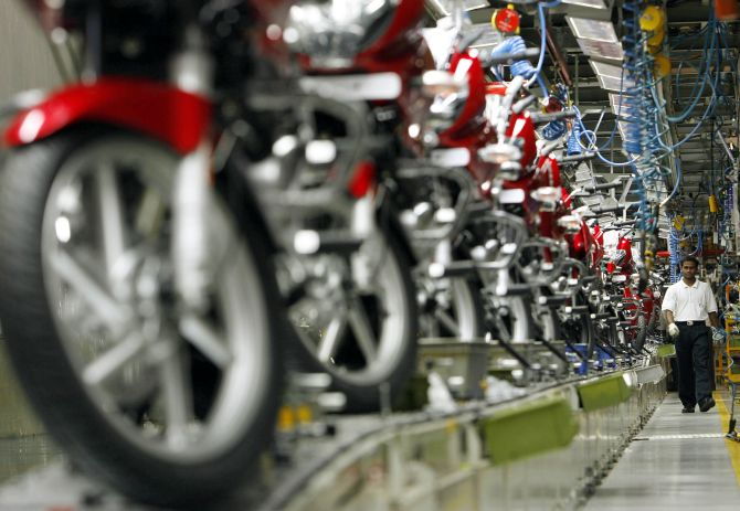 A worker walks beside newly built motorbikes at the Bajaj Auto Ltd. plant