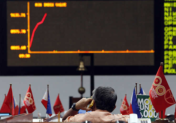 A trader talks to a client in front of a graphic monitor at the Philippine Stock Exchange in Manila. Photo is for representation purpose only.