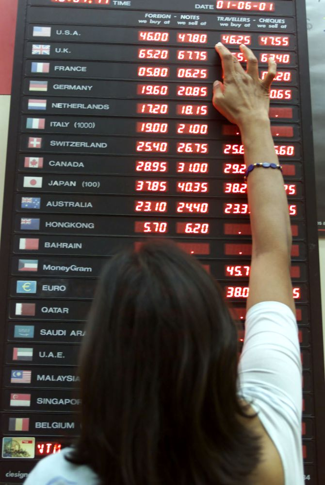 A woman checks the rupee-dollar exchange rate at a foreign exchange bureau.