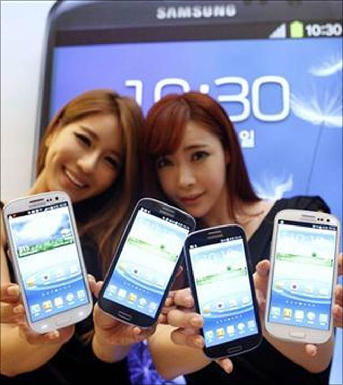 Models hold new Galaxy S III devices as they pose for photographers during an event to launch the smartphone in Seoul.