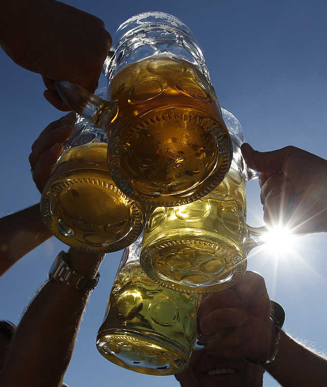 People toast with beer mugs at Munich's Oktoberfest in Germany.