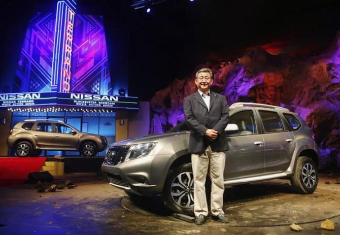 Kenichiro Yomura, CEO of Nissan Motor India, poses with the newly-unveiled Nissan Terrano compact sport utility vehicle in Mumbai.