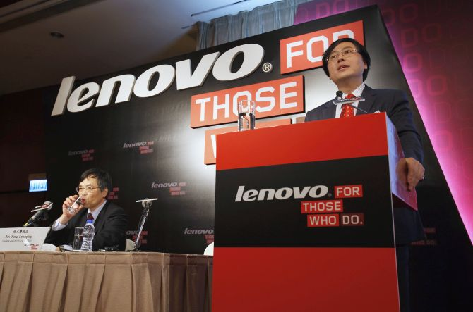 Lenovo Chairman and Chief Executive Officer Yang Yuanqing (R) speaks while attending a news conference on the company's annual results.