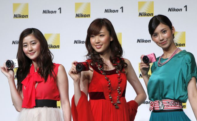 Models pose with Nikon Corp's camera Nikon 1 J1 at its unveiling ceremony in Tokyo.