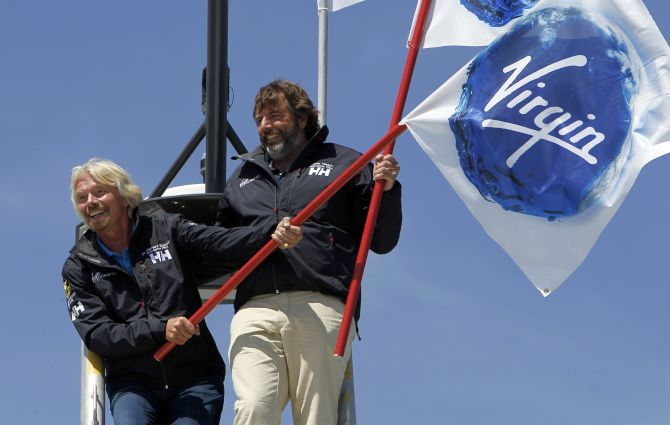 Virgin Group head Richard Branson (L) and explorer Chris Welch stand on the crows nest of the Cheyenne, a 38m (125 ft) catamaran at a news conference in Newport Beach, California.