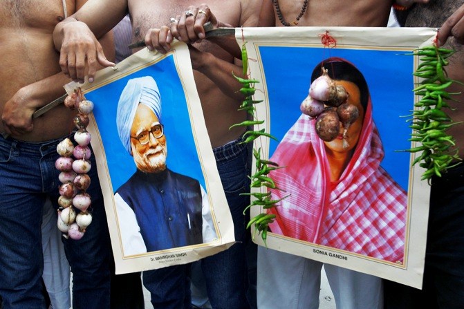 Activists from Bharatiya Janata Party hold garlands of onions and green chillies around portraits of India's Prime Minister Manmohan Singh (left) and Congress party chief Sonia Gandhi during a protest against price hike in onions, in Allahabad.