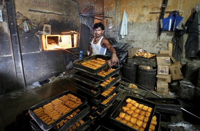 A worker keeps baked rusks after taking them out from an oven at a bakery in Mumbai.
